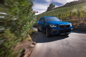 BMW X3 in Blue Driving Around Bend in Road