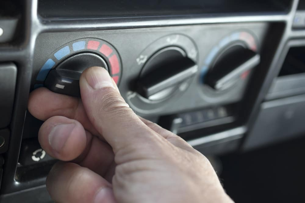 A close up shot of someone's thumb turning the air conditioning setting colder in a car.