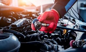 A service technician wearing red service gloves performing Car Air Conditioning Repair on a vehicle.