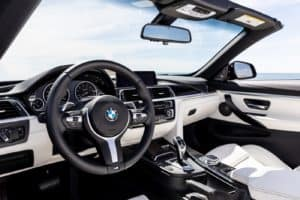 A close up of the BMW 4 Series dash with its leather driving wheel, odometer dash, and infotainment system the prime subjects in the photo.