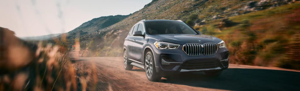 A new gray BMW X1  driving down a dirt dessert road with red sand and hills off in the distance.