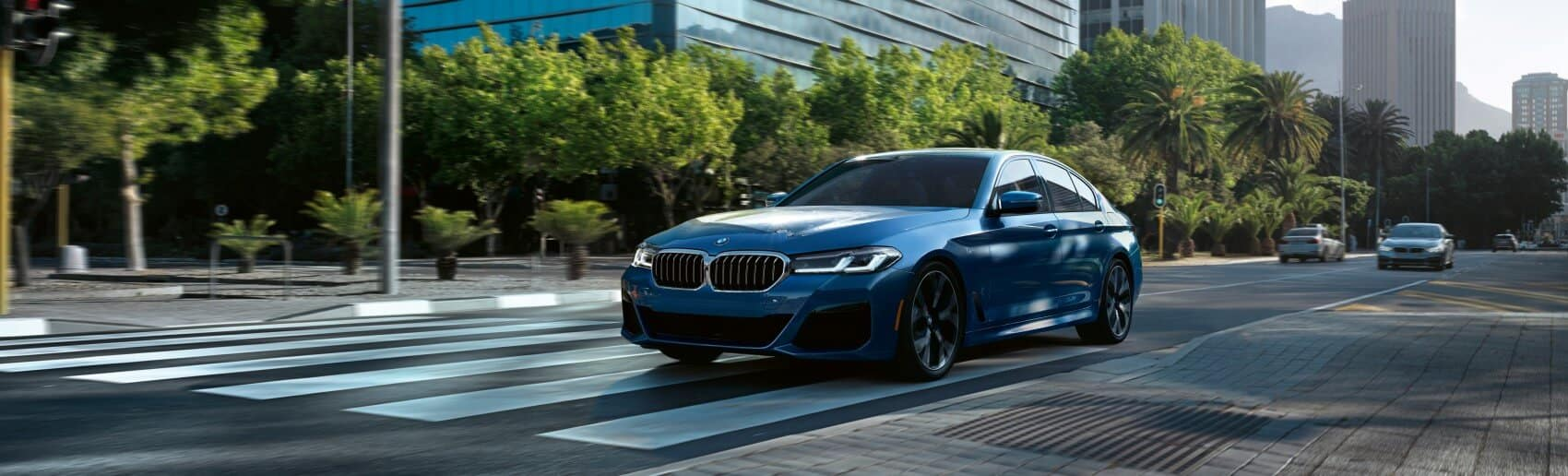 A new 2021 royal blue BMW 5 Series driving down the highway on a sunny day.