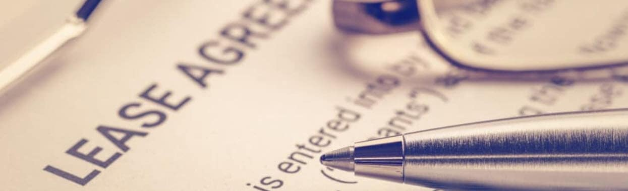 A close up of someone's hand signing a lease contract with a silver pen.