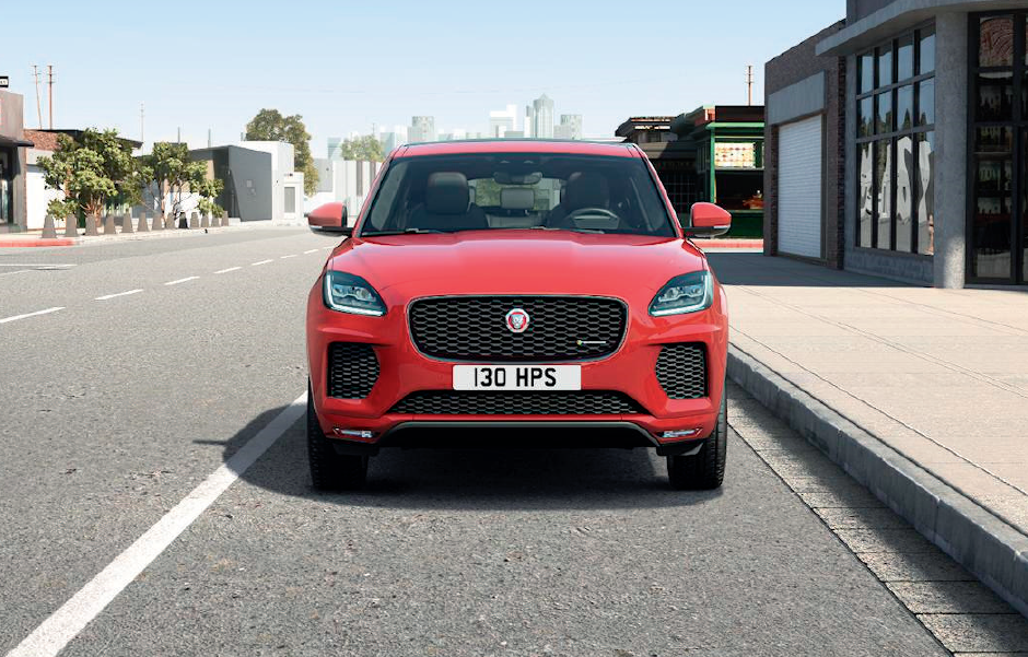 RED JAGUAR E-PACE DRIVING DOWN ROAD IN CITY