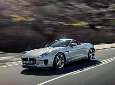 SILVER 2020 JAGUAR F-TYPE CONVERTIBLE DRIVING DOWN ROAD THROUGH MOUNTAIN RANGE