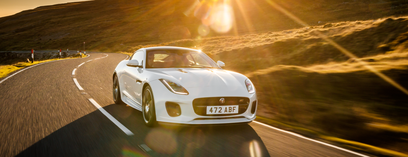 WHITE 2020 JAGUAR F-TYPE COUPE DRIVING DOWN ROAD DURING SUNSET