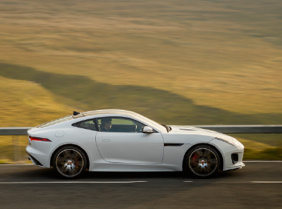 WHITE 2020 JAGUAR F-TYPE COUPE DRIVING DOWN ROAD IN COUNTRY SIDE.