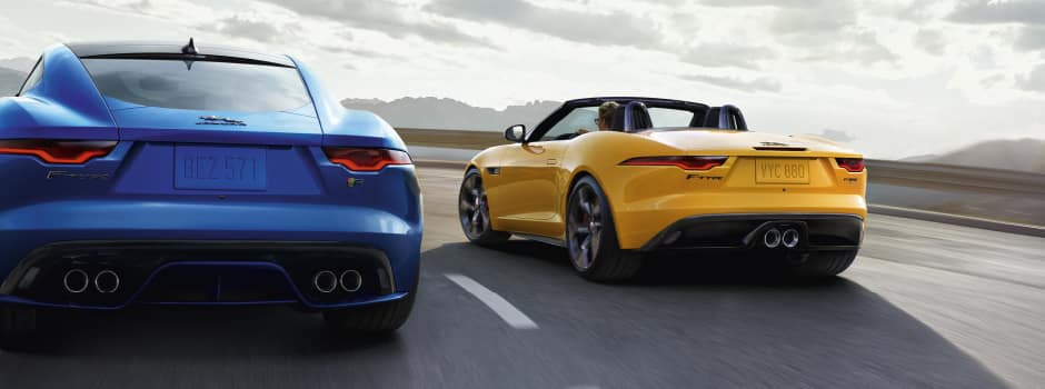 BLUE JAGUAR F-TYPE COUPE AND YELLOW JAGUAR F-TYPE CONVERTIBLE DRIVING DOWN ROAD.