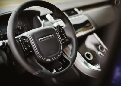 INTERIOR VIEW OF RANGE ROVER SPORT DRIVER'S SEAT INCLUDING THE BLACK STEERING WHEEL.