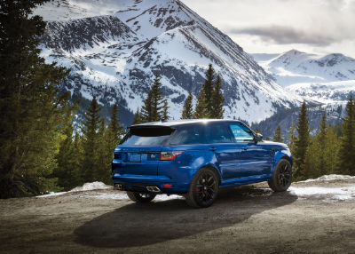 BLUE RANGE ROVER SPORT PARKED NEAR MOUNTAIN AND TREES.