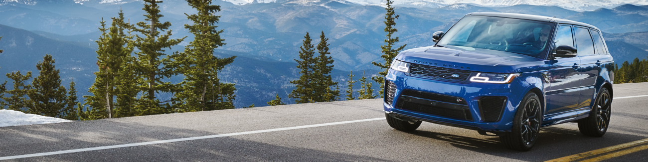 BLUE RANGE ROVER SPORT DRIVING DOWN ROAD NEAR MOUNTAIN RANGE AND TREES.