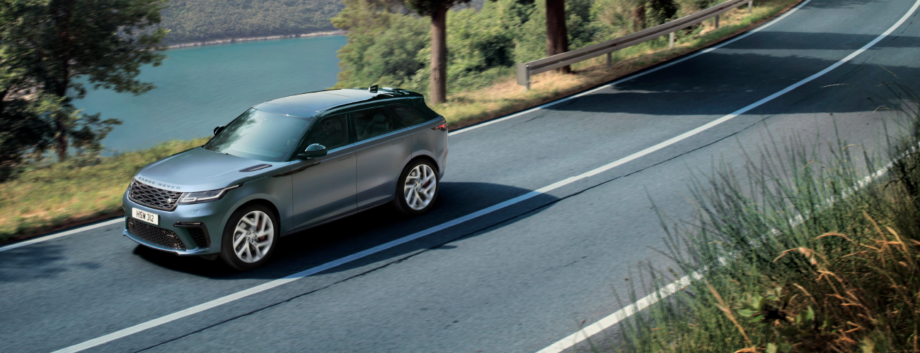 Blue Rover Rover Velar driving down road near lake.