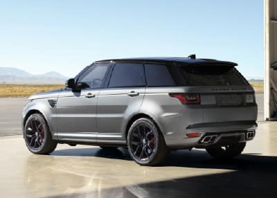 Silver Range Rover Sport driving through desert.