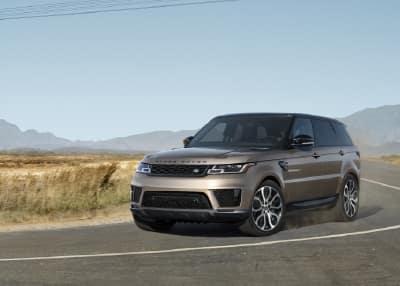 Brown Range Rover Sport driving through desert.