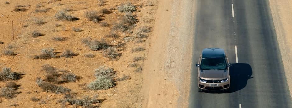 Brown Range Rover Sport driving down road in desert.