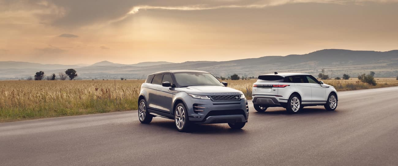 Two Range Rover Evoque models parked near grassy field.