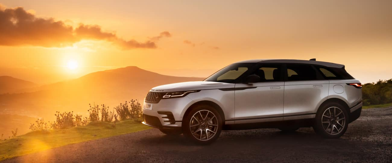SILVER RANGE ROVER VELAR PARKED IN THE MOUNTAINS AT SUNSET.