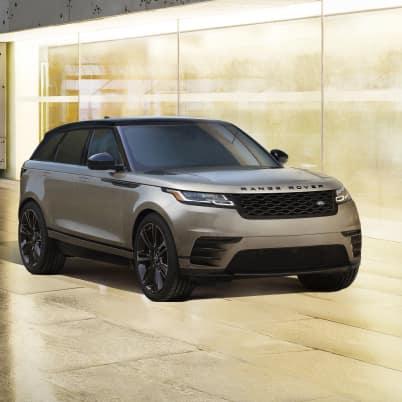 Brown Range Rover Velar parked in city.
